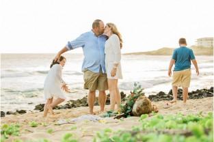 parents kissing two children playing Kauai beach Shipwrecks